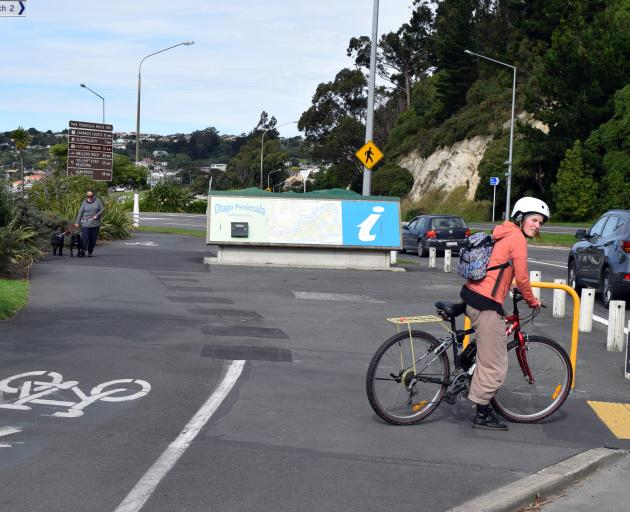 A cyclist waits to cross Portsmouth Dr near the Otago Peninsula map layby area on Tuesday. PHOTO: SHAWN MCAVINUE