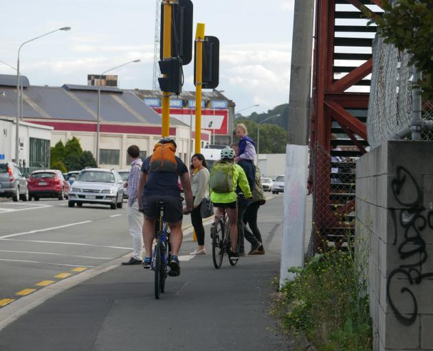 Pedestrians wait at the crossing in Thomas Burns St as cyclists head south on the footpath by the overbridge. PHOTO: JESSICA WILSON