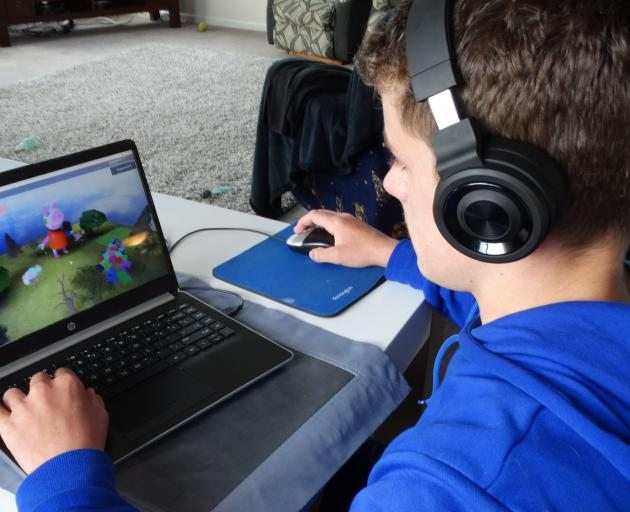Dunedin teenager Jordan Spiers (13) demonstrates game­play while wearing headphones. Hearing Support Otago is targeting hearing loss through headphone-use among young people this month. PHOTO: BRENDA HARWOOD