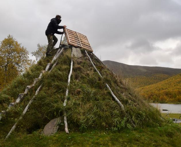 Mikael Vinka stands on top of a traditional goathie home at his Sami Ecolodge near Ammarnas,...
