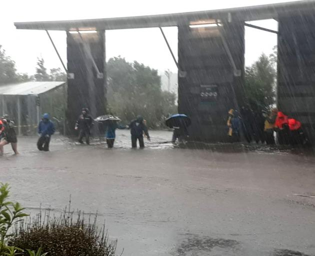 Tourists scramble for shelter from heavy rain at the Real Journeys Milford Sound visitors terminal. Photo: Emergency Management Southland