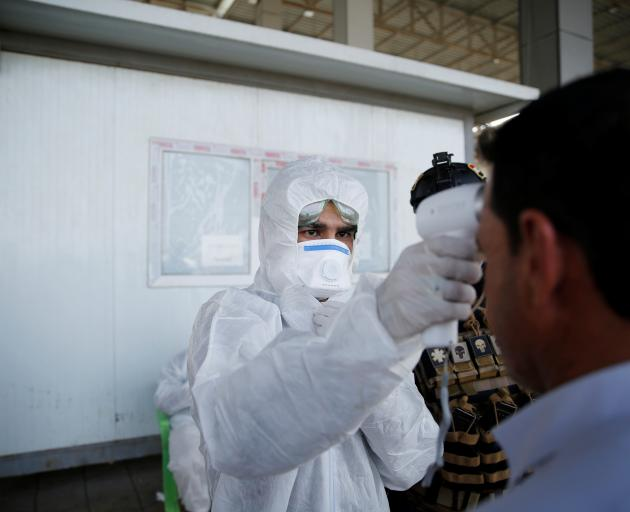 A member of the medical team checks the temperature of an Iraqi man, at the entrance checkpoint...