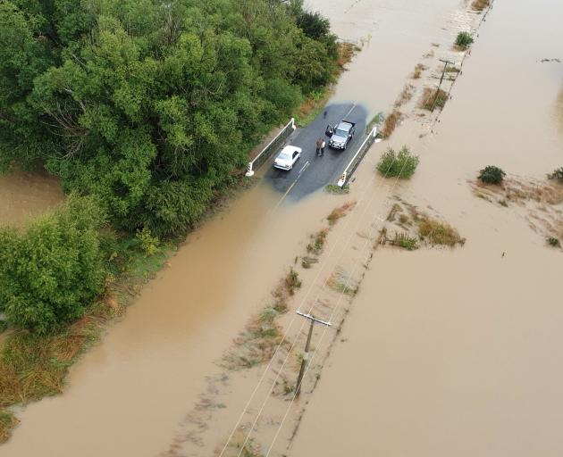 Two motorists find a dry refuge in the Mataura area. Photo: High Country Helicopters
