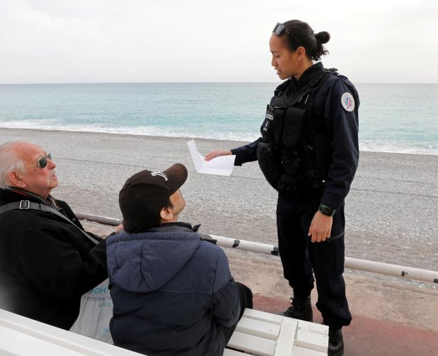 People show their attestation to French police patrolling on the Promenade des Anglais in Nice on...