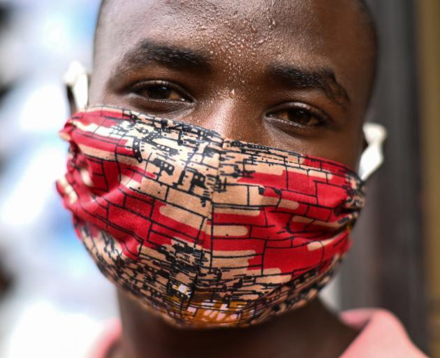 "Pierre Mahiraguha, a vendor at the Kimironko market wears a handmade ""kitenge"" cloth mask in..."