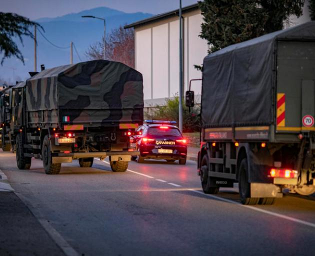 Military trucks drive through streets of Bergamo in northern Italy after the army were deployed...