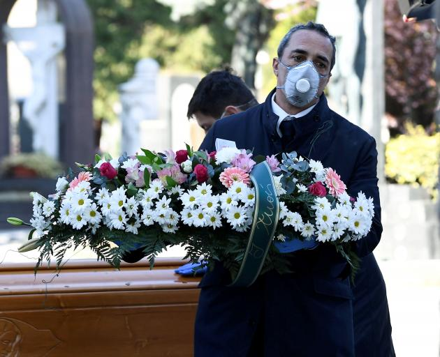 Cemetery workers and funeral agency workers in protective masks transport a coffin of a person...
