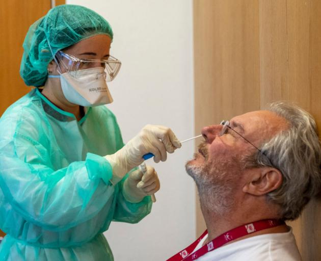 A health technician wearing protective gear takes a swab from a patients nostrils at a Covid-19...