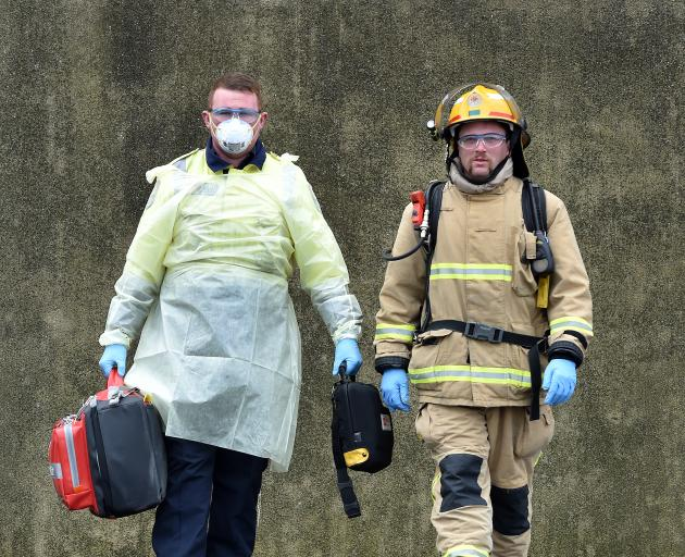 Career Firefighters Mat Loughney (left) wears personal protective equipment and Jules Bennett fire callout gear at the Dunedin Central Fire Station on Tuesday. Photo: Peter McIntosh