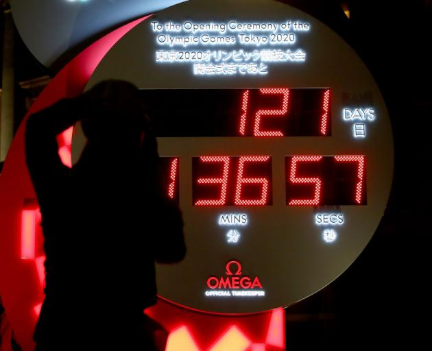 People in Tokyo watch the official Olympic countdown clock with the remaining days and time until the 2020 Summer Olympics after it was announced yesterday that the Games will be postponed until 2021 due to the coronavirus outbreak. Photo: Getty Images
