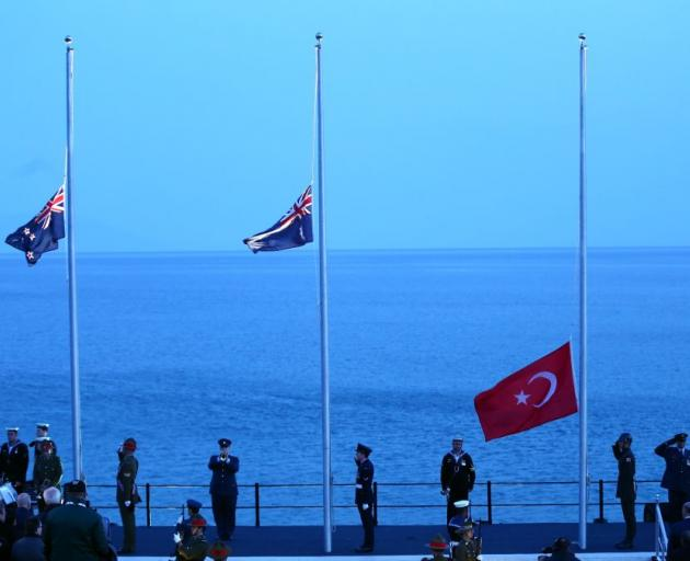 NZ, Australian and Turkish flags are raised the dawn service at Anzac Cove on the Gallipoli...