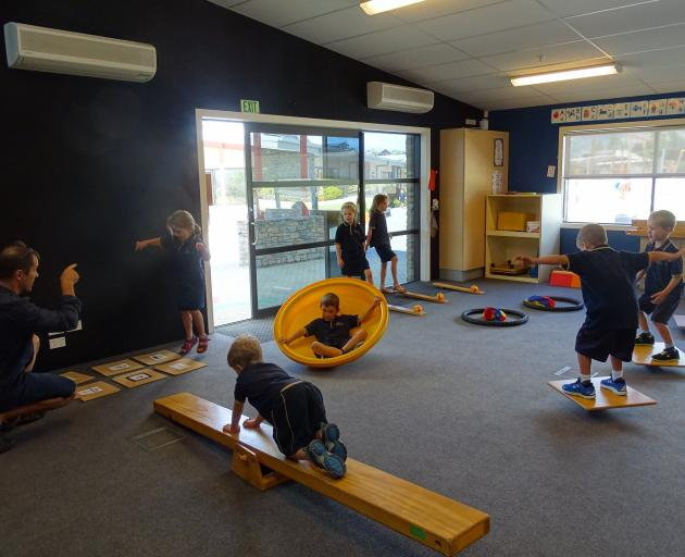 Wanaka primary AP Jason Cowan works with children from room 12 year 2 on their skipping, crawling...