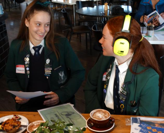 Columba College prefects Hannah Clarke (17, at left) and Isobel Fraser (16) try to communicate...