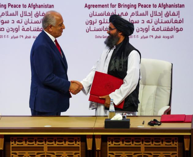 Mullah Abdul Ghani Baradar, the leader of the Taliban delegation, and Zalmay Khalilzad, U.S. envoy for peace in Afghanistan, shake hands after signing an agreement at a ceremony between members of Afghanistan's Taliban and the US. Photo: Reuters