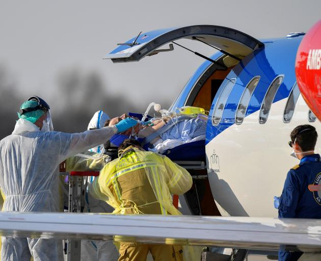 A coronavirus infected patient from France is transferred from an ambulance aircraft to an...