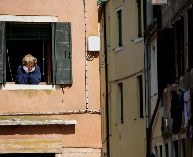 A woman looks out of an apartment window in Venice as Italians remain under lockdown. Photo:...