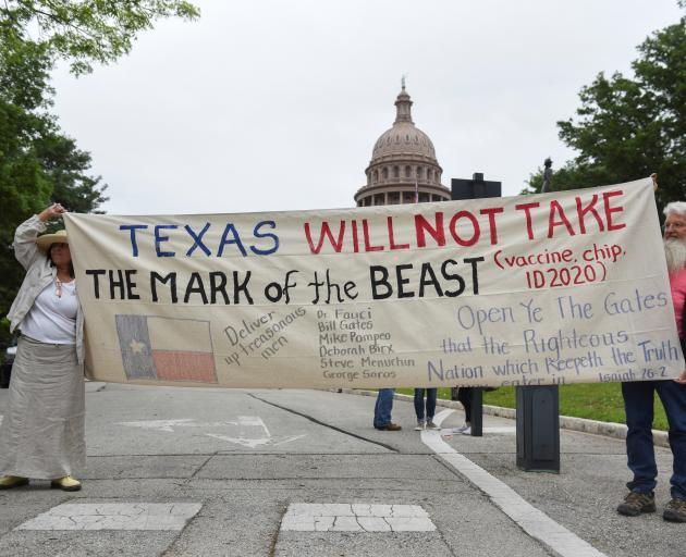 People protesting against the state's extended stay-at-home order demonstrate at the Capitol...