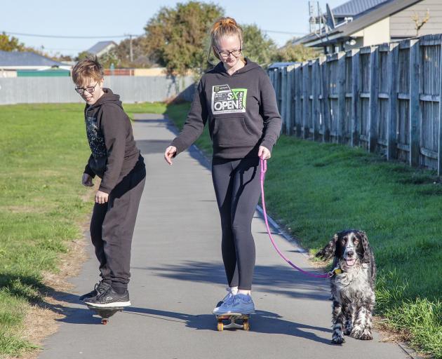 Skateboarding and exercising the dog at the Rawhiti School bike track, New Brighton.