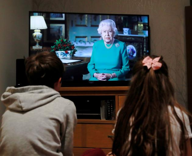 Noah (9) and Milly (7), of Hertford, watch Queen Elizabeth during a televised address to the...