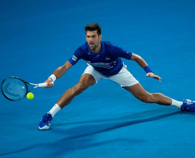 Novak Djokovic reaches for a shot during his win last night at the Australian Open. Photo: Getty...