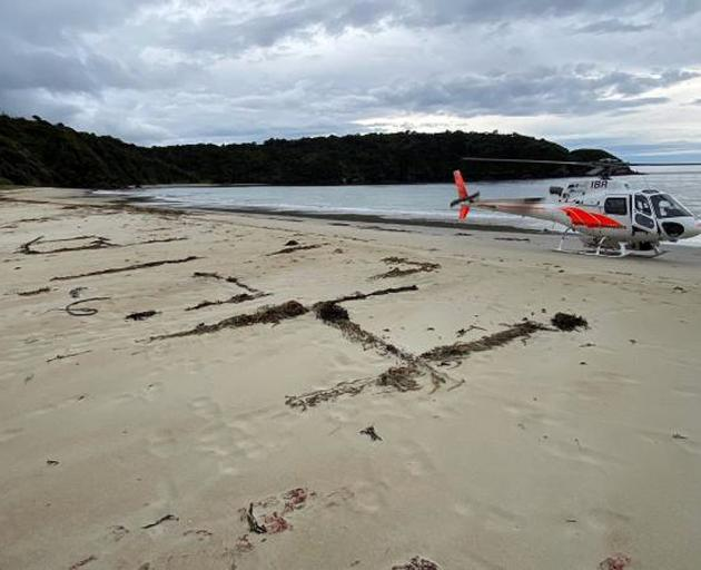 Eli Smith wrote a message in the sand as he waited to be rescued. PHOTO: SUPPLIED