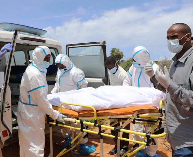 Somali workers in protective suits and civilians prepare to carry the body of a man suspected to have died of the coronavirus disease during the outbreak in Somalia. Photo: Reuters