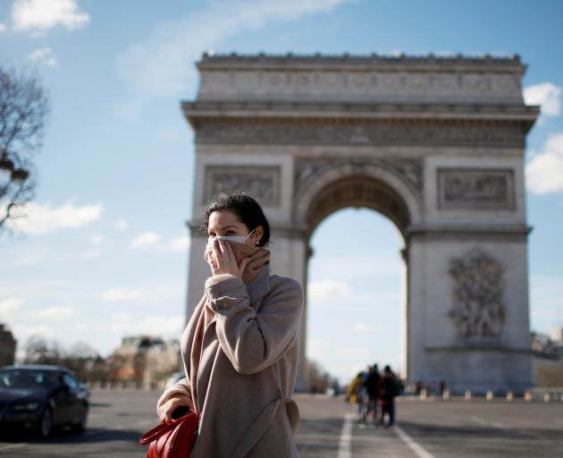 A woman wearing a protective mask, walks near Arc de Triomphe as France grapples with an outbreak...