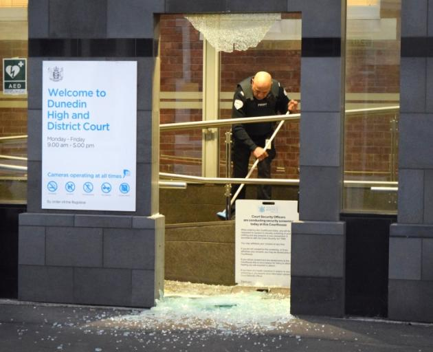 A security guard sweeps up the glass.