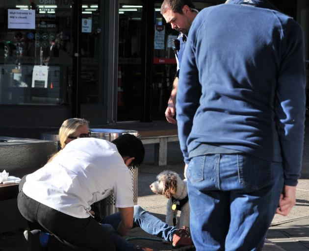 Pharmacist Chin Loh helps a customer who was bitten by another customer's dog outside the...