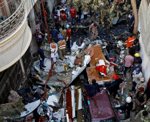 Rescue workers gather at the site of a passenger plane crash in a residential area near an airport in Karachi. Photo: Reuters