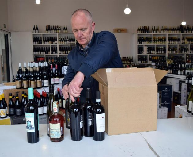 Wine Freedom co-owner Paul Williams packs a box of wine in his shop in Dunedin's Warehouse Precinct. PHOTO: SHAWN MCAVINUE