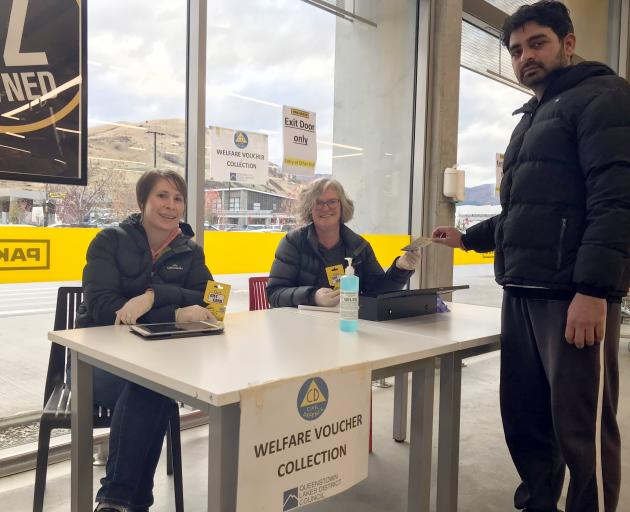 Parmuir Kumar picking up a food voucher in Queenstown yesterday from volunteers Amanda Peters and...