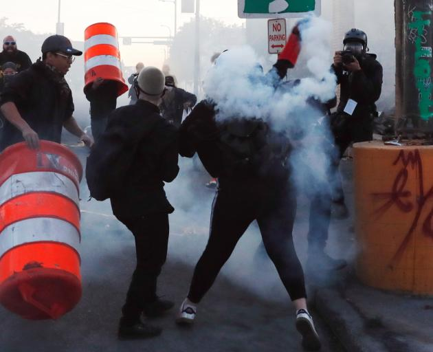 A protester throwing tear gas during continued demonstrations in Minneapolis on Monday. Photo:...