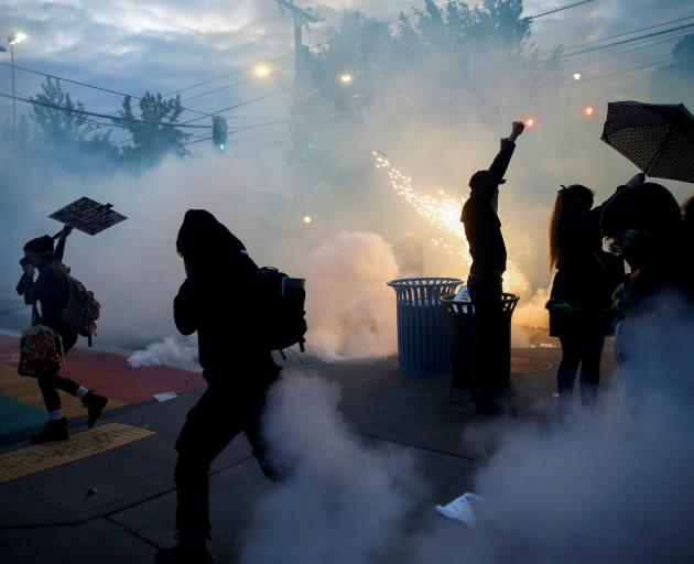 Protesters disperse as tear gas, pepper spray and flash-bang devices are deployed by Seattle...
