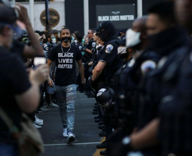 A demonstrator walks past police officers near Black Lives Matter Plaza in Washington. PHOTO:...