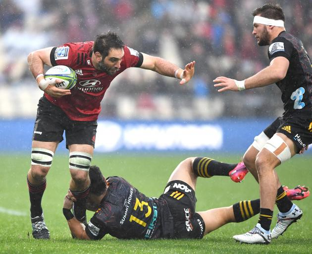 Sam Whitelock looks to fend during a wet afternoon in Christchurch. Photo: Getty Images