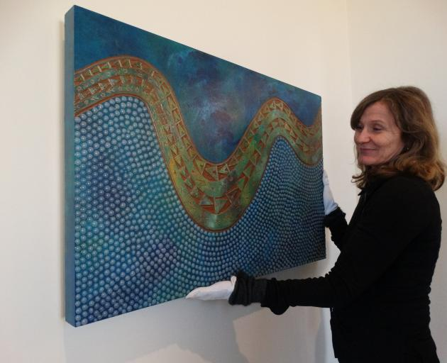 Colourful . . . Forrester Gallery director Jane Macknight prepares to hang a piece by Samoan...