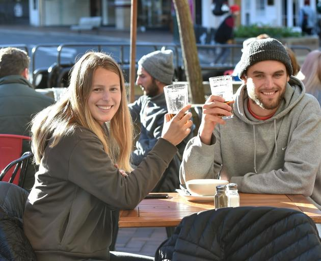 Neve Doak and Max Anderson, both from Auckland, enjoy a drink in the Octagon on Saturday before...