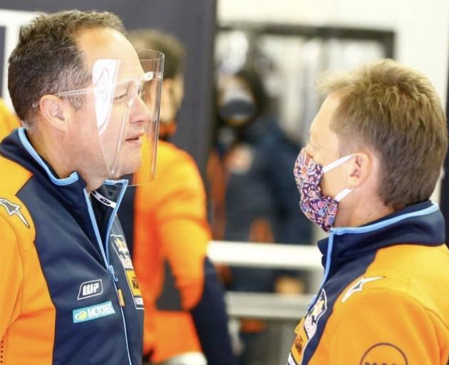 Paul Trevathan (left) wears a face mask while talking to KTM team manager Mike Leitner during...