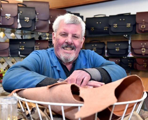 Bill Drake in the Rattray St store in 2015, with a full display of satchels behind. 