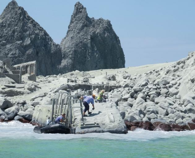 White Island tour operators carry out a rescue operation on the island. Photo: Michael Schade