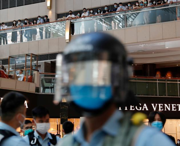 Riot police patrol at a shopping mall during a protest after China's parliament passes a national...