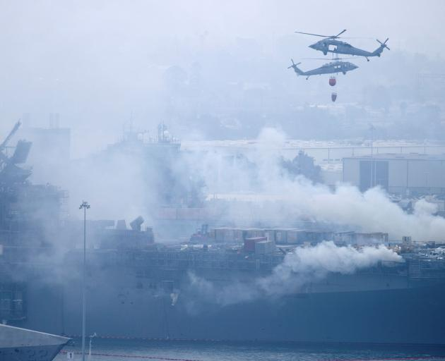 US Navy helicopters and city firefighters continue fighting a fire on the amphibious assault ship USS Bonhomme Richard. Photo: Reuters