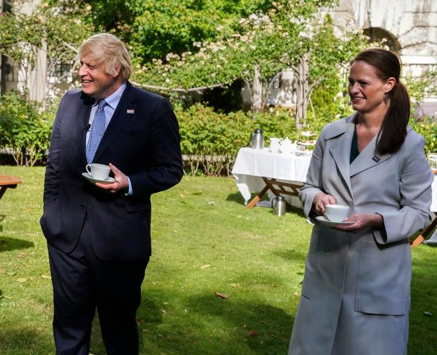 British Prime Minister Boris Johnson enjoys a cup of tea with nurse Jenny McGee, who is from...