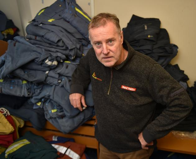 Paul Harrington surrounded by uniforms his dry-cleaning company cleans for New Zealand Aluminium...