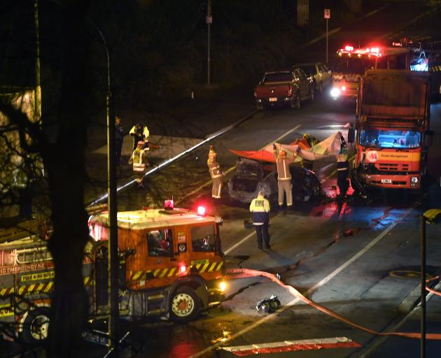 Firefighters assist at the scene of a double fatality crash between a car and a truck near a...