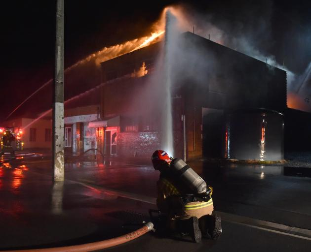 Firefighters tackle a blaze at the old Wolfenden and Russell building in South Dunedin on...