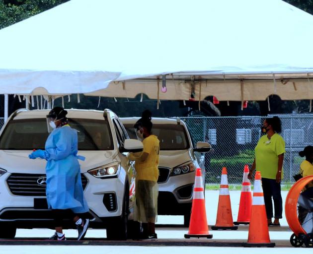 People are tested for Covid-19 at a drive through site operated by the Florida Department of...