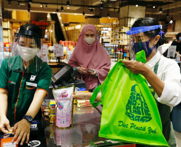 A worker wearing a face shield and protective mask use a tote bag to replace plastic at a...