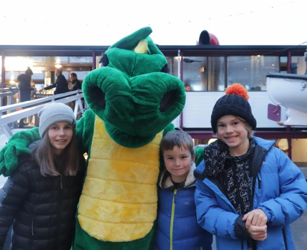 Maggie, Finn and Sam Langford enjoy being greeted by Pot the Dragon before boarding TSS Earnslaw....